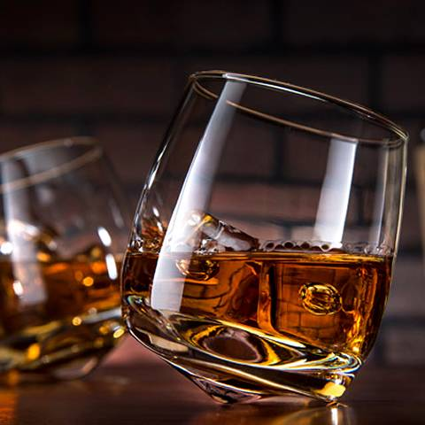 There are two blown tumbler drinkware roly-poly rolling rocking glass cups are filled with ice cubes and whiskey wine.