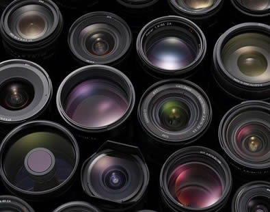 Many sizes of camera lenses are on the ground.