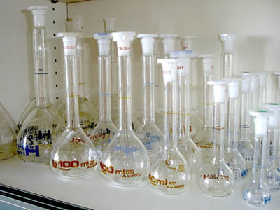 Many capacity bottles of different sizes are placed on a desk.