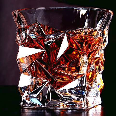 The diamond shaped whiskey glass is full filled with whiskey wines.
