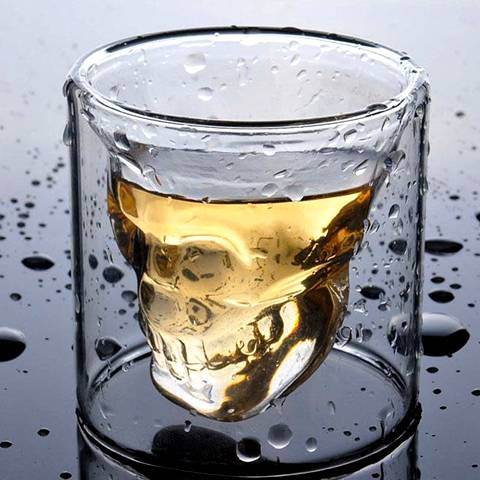 The double wall tumbler skull glass cup is full filled with whiskey wines.
