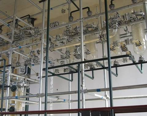 The huge distillation equipment with many glass coil pipe condensers in pharmaceutical factory.