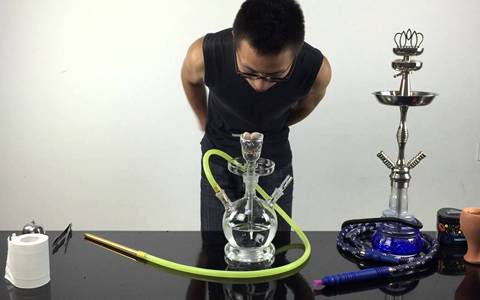 A people is observing the situation of carbon that used in glass hookah.