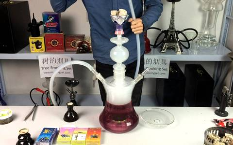 A people is smoking with glass hookah that has blueberry juice.