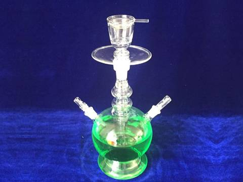 A glass hookah with green liquid on blue tablecloth.