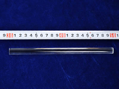 A hand is measuring glass rod length with meter ruler.