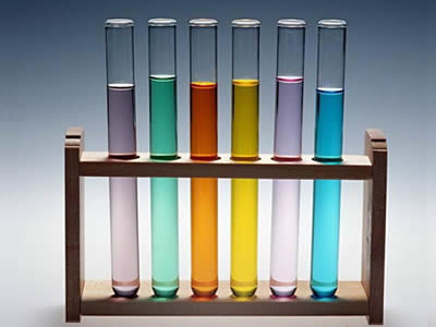 Six glass test tubes with different solutions on the test tube rack.