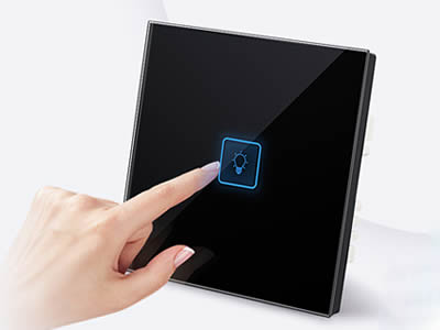 A finger is pressing lamp button on the switch.