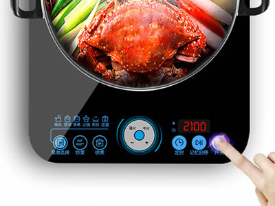 A finger is pressing buttons on the induction cooker.
