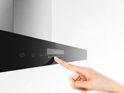 A finger is pressing button on the range hood.