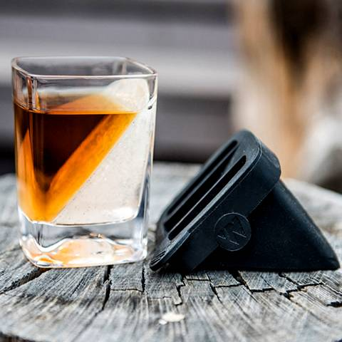 There is a square whiskey glass with whiskey wine and a silicone ice form.