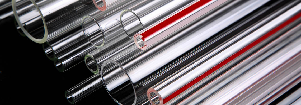 A variety of transparent glass tubes and some with red of different sizes are placed together.